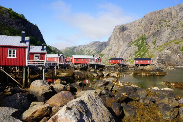 Rote Holzhäuser auf Stelzen am Fjord